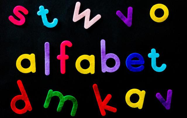 """Färgade bokstäver mot svart bakgrund där några av bokstäverna bildar ordet """"alfabet""""."""