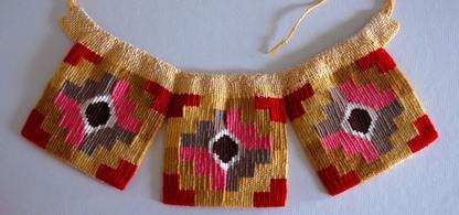 Ett vävt halssmycke med tre mönstrade kvadrater som hänger från ett halsband med mönster i gult, rött, rosa, svart, grått och vitt.