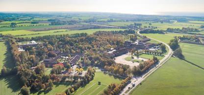 Flygbild över Munkagårdsgymnasiet med havet i horisonten.