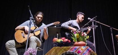 Hadi Ali och Farhad från Songlines spelar gitarr på en scen.