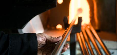 Glasblåsarens hand och glas i ugnen.