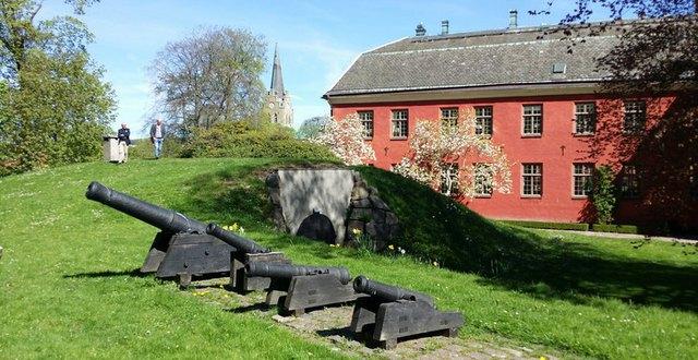 Slottsträdgården vid Halmstads slott med fyra kanoner i förgrunden, två personer skymtar långt bak i bilden.