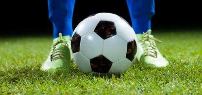 Benen av en fotbollsspelare med benskydd och blå strumpor som står på en gräsplan och har en fotboll mellan fötterna. Bakgrunden är svart.