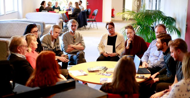 En grupp personer sitter omkring ett runt bord och lyssnar uppmärksamt på en i gruppen som pratar. I bakgrunden syns ännu en grupp runt ett annat bord.
