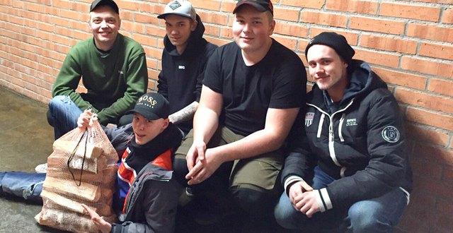 Fem elever poserar med en säck ved.