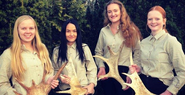 Fyra elever i skogen med varsitt älghorn.