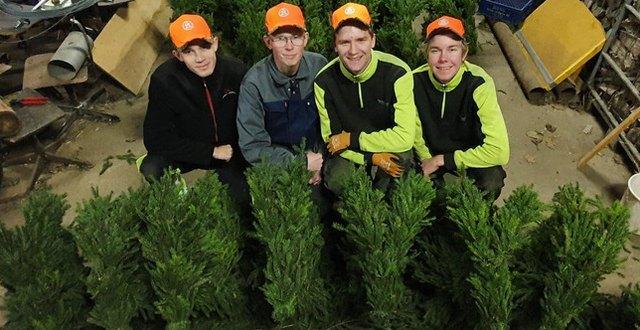 Fyra elever bakom sina julbockar av granris.