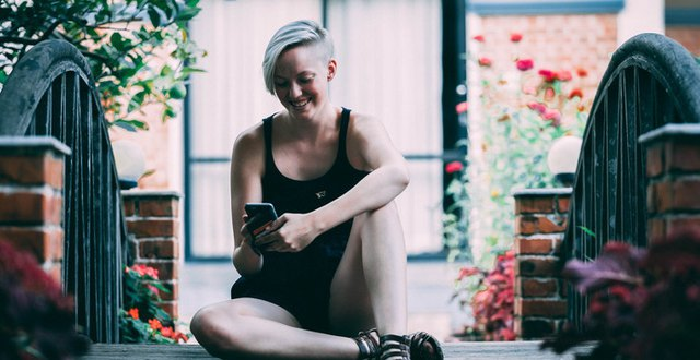 Alida Svensson, en ung kvinna sitter på en bro och tittar på en mobiltelefon som hon har i händerna.
