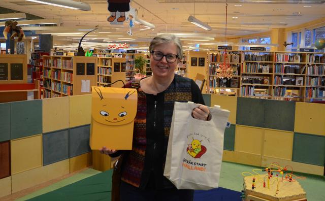 Christina Söderstedt står i biblioteket och håller fram de två första språkpaketen i form av en låda och en kasse.