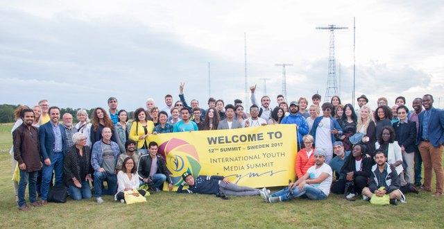 Gruppfoto deltagare i internationellt läger för unga och unga vuxna, framför masterna vid Grimeton Radiostation.