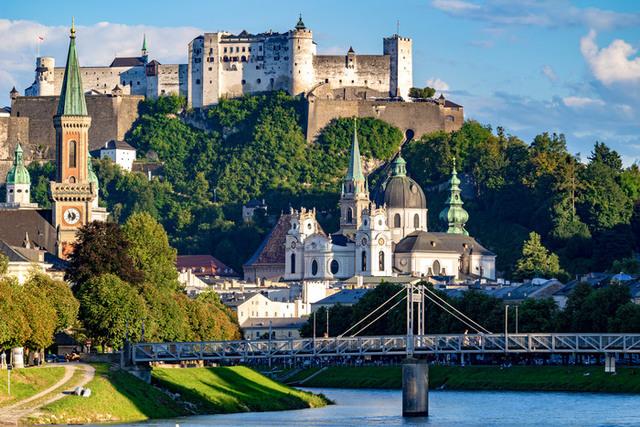 Vy från Salzburg med en stor borg på ett berg i bakgrunden, en flod i förgrunden, kyrkor och byggnader med tinnar och torn, samt bostadshus vid floden.
