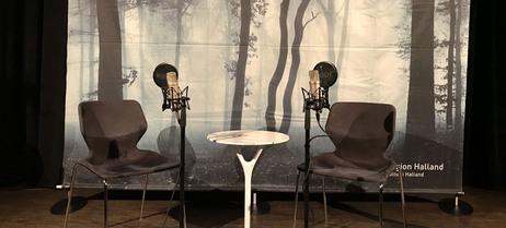 Scenen står redo för konstsamtal med två stolar och två mikrofoner.