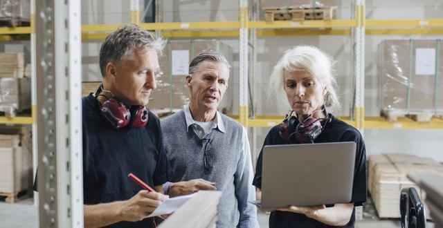 tre personer i en lagerlokal, samtalar och tittar på en datorskärm