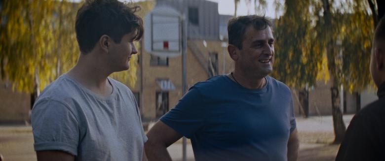 En ung man står bredvid och tittar mot en medelålders man.