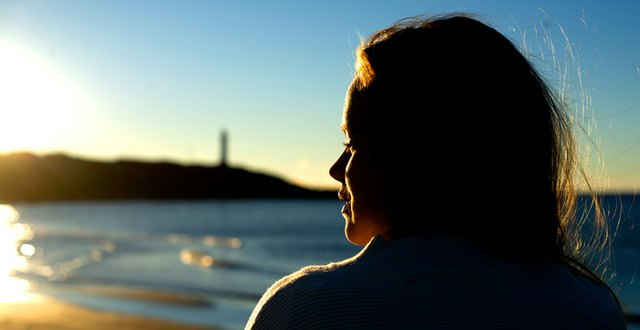 Flicka vid havet i Varberg, fotograferad i profil i motljus.