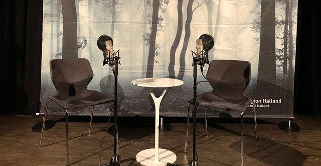 En scen med två stolar och två mikrofoner på varsin sida om ett litet bord.