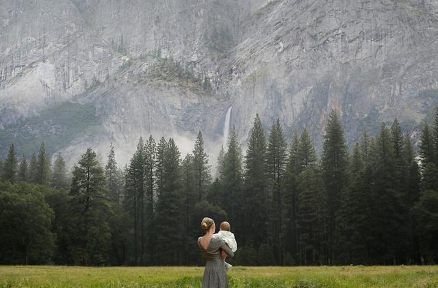 En kvinna som bär sitt barn och tittar ut över skogen.