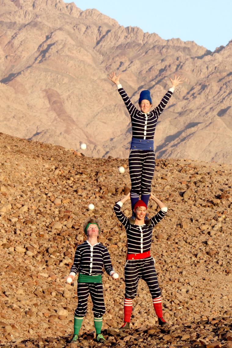 Tre personer i svarta kläder med vita ränder och detaljer i respektive grönt, rött och blått. En av dem jonglerar med bollar, den andre står på den tredje personens axlar.