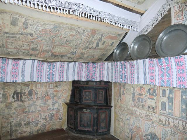 Interiör från Bollaltebygget med opphämtaväv och bonadsmålningar längs väggen.