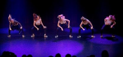 Fem unga dansare på en scen.