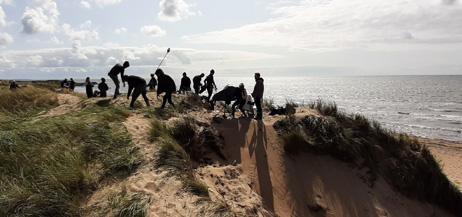 Filminspelning i sanddyner vid havet.