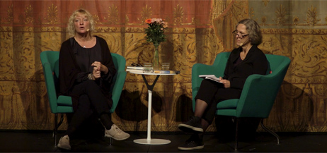 Anna Takanen och Marit Kapla sitter i fåtöljer på en scen.