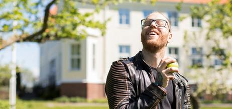 En kille med äpple i handen står i en park framför vit skolbyggnad.
