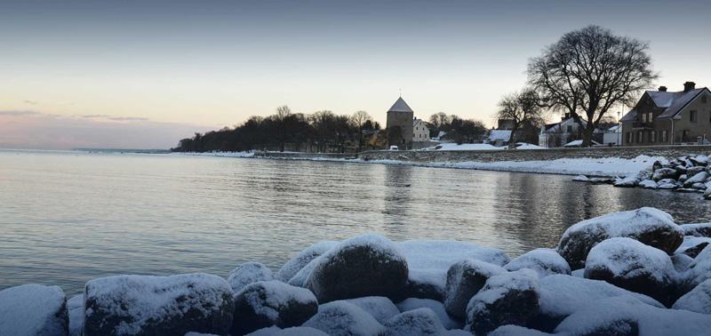 Kruttornet i Visby med havet framför och snö på marken.