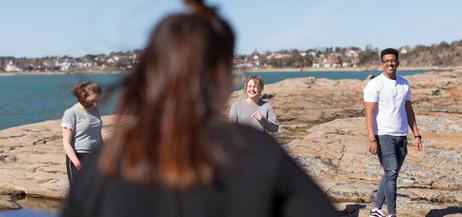 Fyra personer på klipporna framför en havsvik.