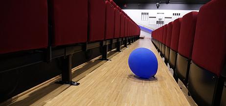 En blå ballong på golvet mellen två tomma stolsrader i salong.