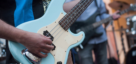 Närbild på hand som spelar på en ljusblå elgitarr, fler musiker skymtar i bakgrunden.