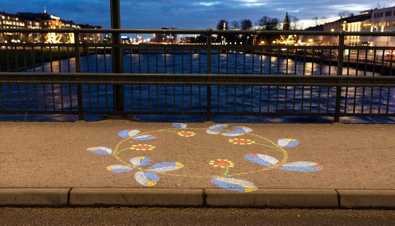 En färgglad broderad blomsterkrans projiceras på gångbanan på Österbro i Halmstad.