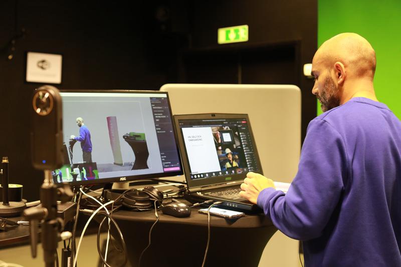 En person står framför två datorskärmar i en studio.