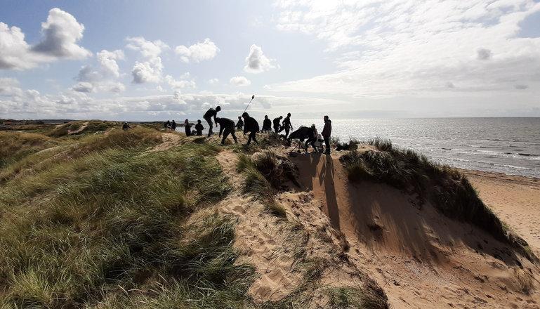 Filminspelning med flera personer på toppen av en sanddyn vid havet.