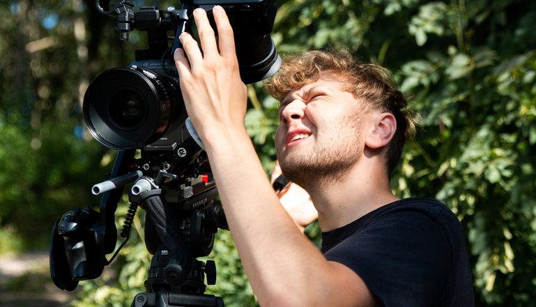 En kille med kamera står och kisar mot solen och tittar i sökaren.