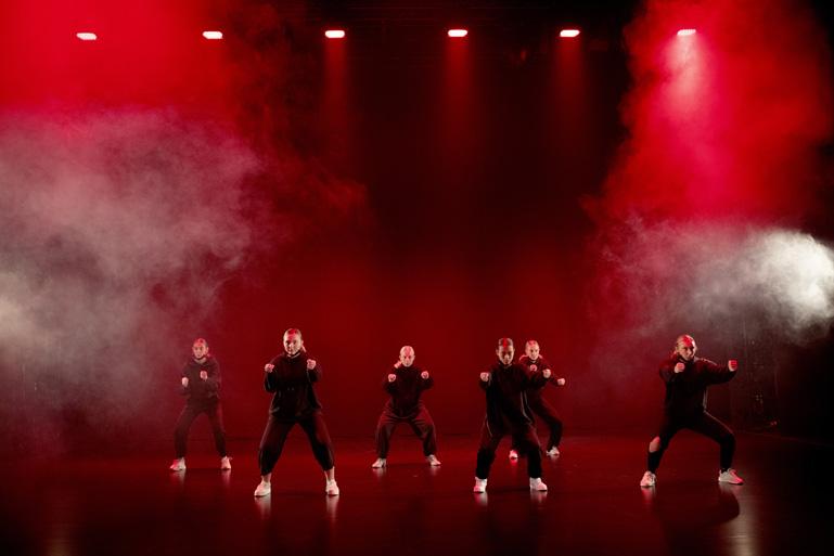 Dansgrupp i svarta kläder på en scen med rök och upplyst med rött ljus.