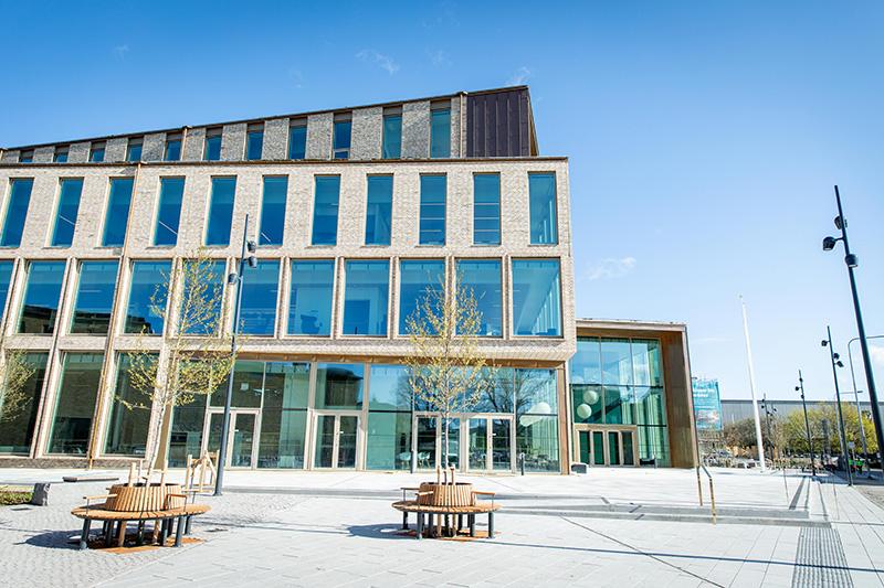 En stor byggnad i fyra våningar med stora glaspartier.