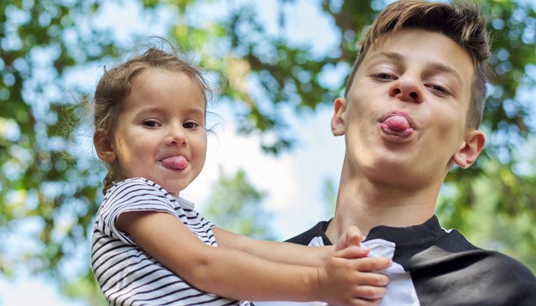 Ett litet barn och en tonåring ler och räcker ut tungan.
