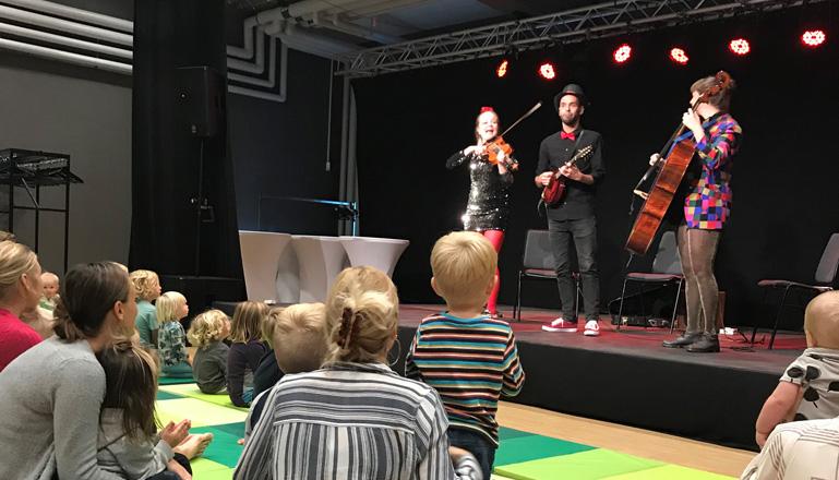 Musikföreställning på scen och små barn med vuxna i publiken.