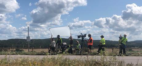 Ett filmteam arbetar vid en väg i öppet landskap.