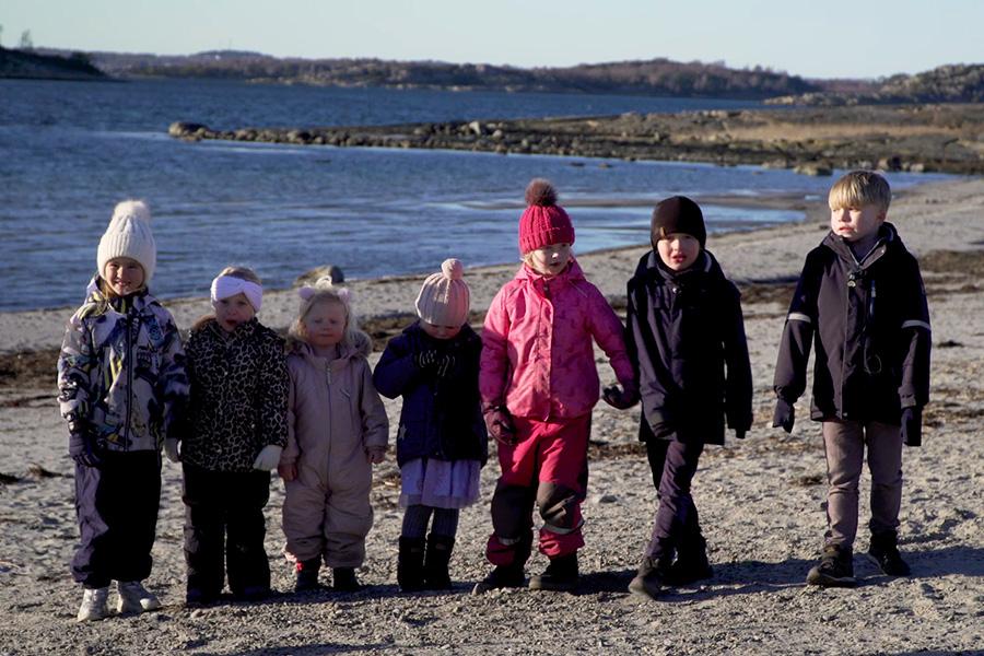 Sju förskolebarn i mössor och vinterkläder på en strand i Åsa, Halland.