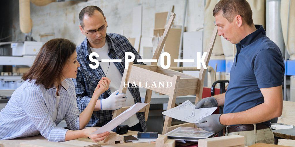 Två män och en kvinna står i en verkstad och tittar på delar en stol och papper.