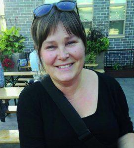 leende kvinna med svart blus och solglasögon i pannan