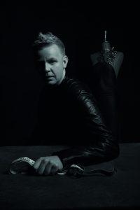 Svartvit bild på en man i halvfigur med ett måttband i handen.