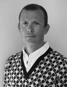 Svartvitt porträtt av man i mönstrad tröja.