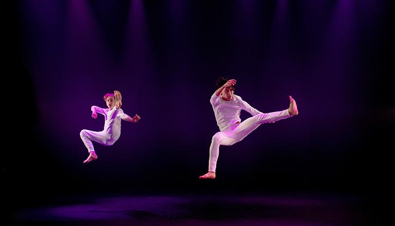 Två killar i vita kläder flyger i luften i ett danssteg.