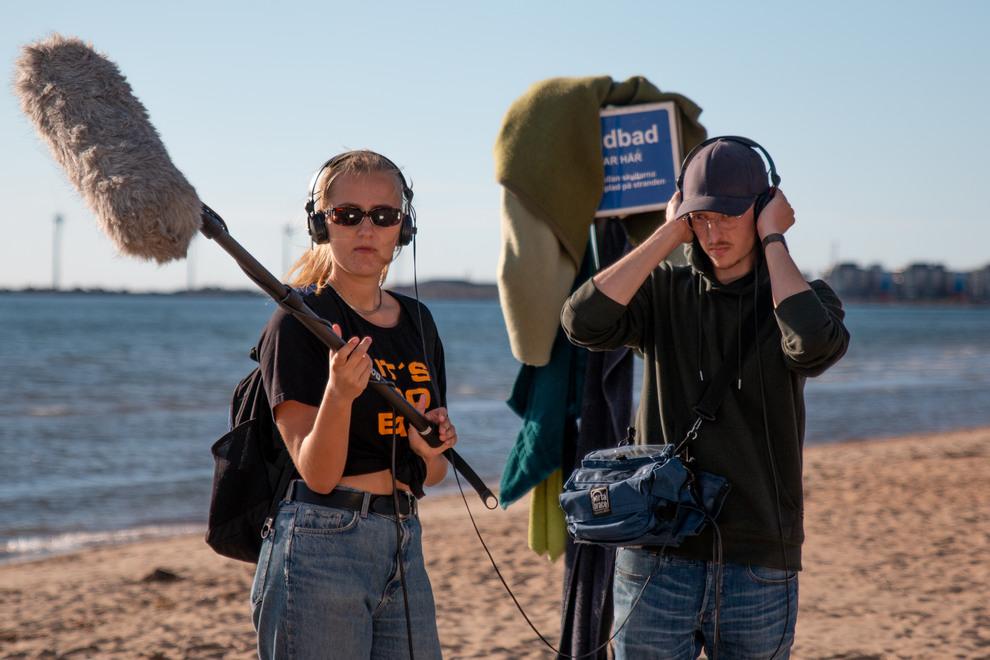Två personer med utrustning för filminspelning på stranden.