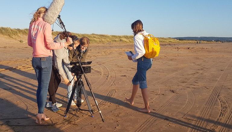 Fyra tjejer spelar in film på en sandstrand.