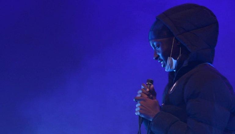 En kille med mikrofon i händerna på en scen.