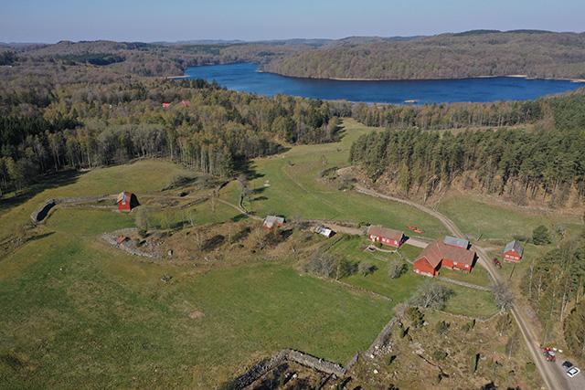 Flygfoto över Björkekullen., en gård med flera byggnader, stengärdsgårdar och med åkrar, skog och en sjö i närheten.